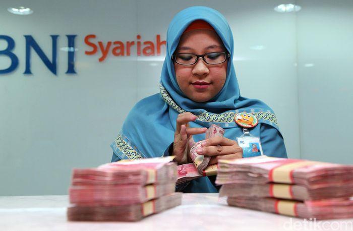 Petugas sedang menghitung uang di BNI Syariah, Jakarta, Selasa (3/1/2017).