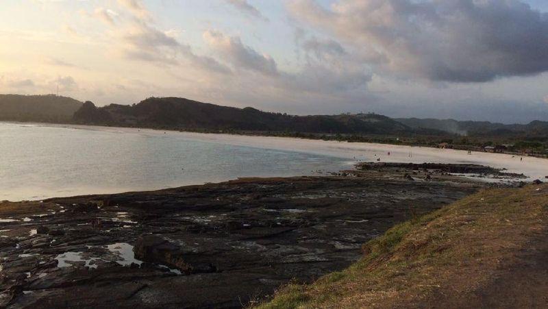 Yang pertama adalah Tanjung Aan. Pantai ini jika dilihat dari atas bukit tampak melengkung dengan cantiknya, berpasir putih dan air lautnya tampak biru kehijauan (Masaul/detikTravel)
