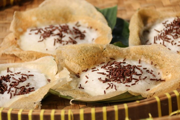 Serabi Solo, pancakes using coconut milk, a popular snack and breakfast item from city of Solo in Central Java region. These are the variant that add some chocolate sprinkles for some chocolatey flavor. These pancakes have thin, wide other rim as they are cooked in woks; which also caused the center part being the thickest and meatiest part. The pancakes are underlined with cut pieces of banana leaves to prevent them from sticking to the tray. A traditional woven bamboo tray is used as the base. This image was taken outdoor and used sunlight as its natural lighting source.