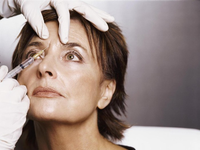 Mature Woman Receiving an Injection to Her Forehead