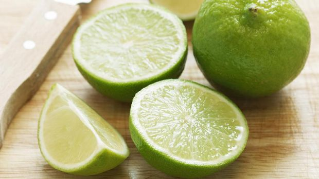 Cut limes and knife on wooden board, close-up