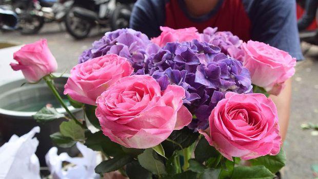 Pekerja merangkai bunga mawar di Pasar Bunga Rawa Belong, Jakarta, Senin (13/2).