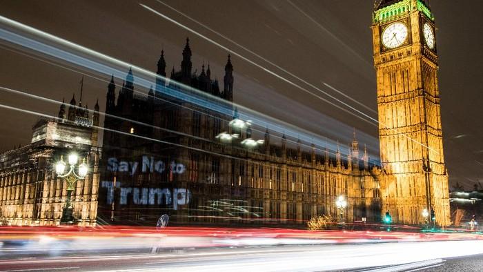 Ada yang terlihat berbeda dari Istana Westminster di London, Minggu (19/2). Gedung parlemen itu menjadi latar dari proyeksi bertuliskan Say No to Trump.