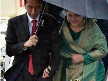 Mesra sekali Jokowi memayungi Iriana sambil berpegangan tangan. (Foto: istimewa)