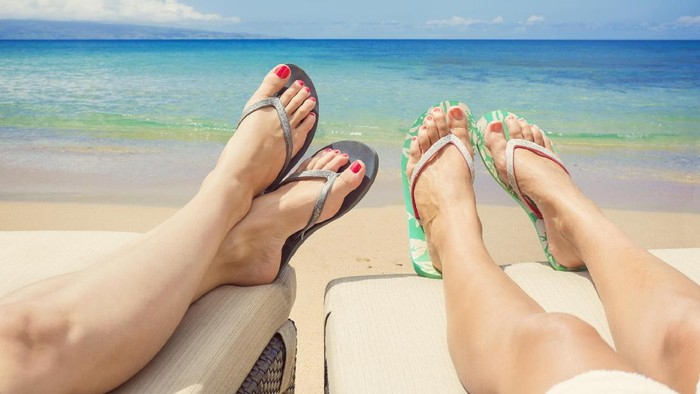 Sandy toes and feet of two women relaxing on chaise lounge chairs while enjoying a tranquil beach vacation. Idyllic Tropical beach resort scene of two women sunbathing
