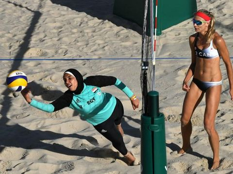 Egypt's Doaa Elghobashy (L) dives for the ball during the women's beach volleyball qualifying match between Canada and Egypt at the Beach Volley Arena in Rio de Janeiro on August 11, 2016, for the Rio 2016 Olympic Games. / AFP PHOTO / Yasuyoshi Chiba