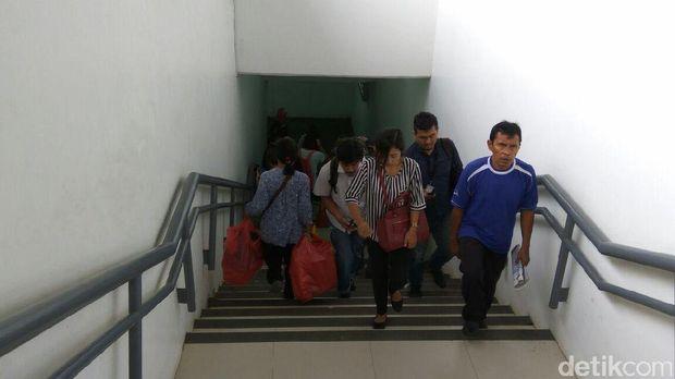 Penumpang menyusuri anak tangga di underpass Stasiun Manggarai.