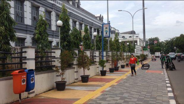 Trotoar ini dihiasi tanaman hias dalam pot warna kuning dan oranye. Ada juga tempat pembuangan sampah di sudut-sudut trotoar.