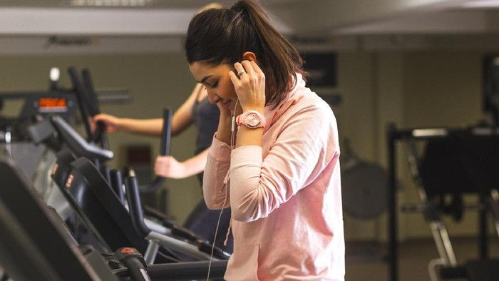 Girl running on the treadmill and listening music at the gym.