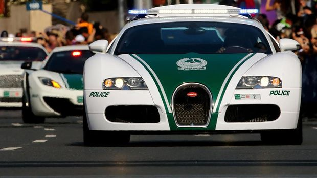 A Dubai police Bugatti leads a convoy of police vehicles: a Lamborghini Aventador and a Bentley as they drive through the streets of downtown Dubai, February 08, 2014.  Dubai police have introduced top end sports cars to their patrol fleet to further strengthen the image of
