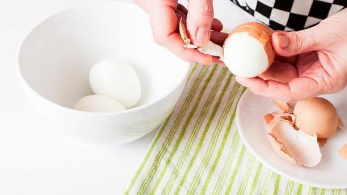 mengupas telur rebus