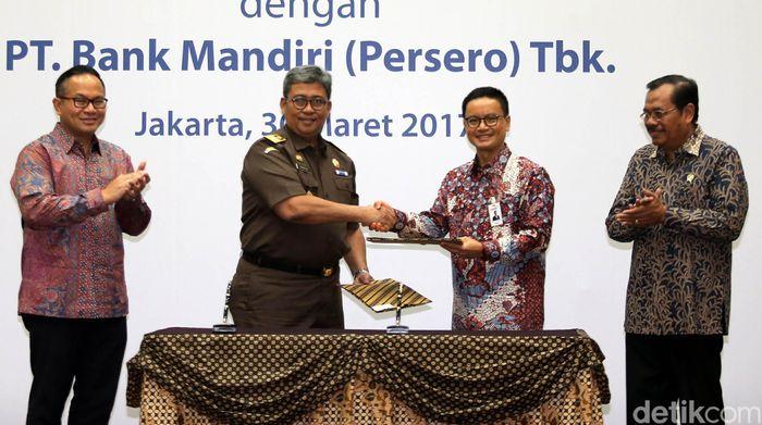 Jaksa Agung HM Prasetyo (kanan) dan Dirut Bank Mandiri Kartika Wirjoatmodjo (kiri) menyaksikan Jampidsus Arminsyah (kedua kiri) dan Direktur Risk Management & Compliance Bank Mandiri A.Siddik Badruddin (kedua kanan) berjabat tangan usai menandatangani perjanjian kerjasama di Jakarta, Kamis (30/3/2017).