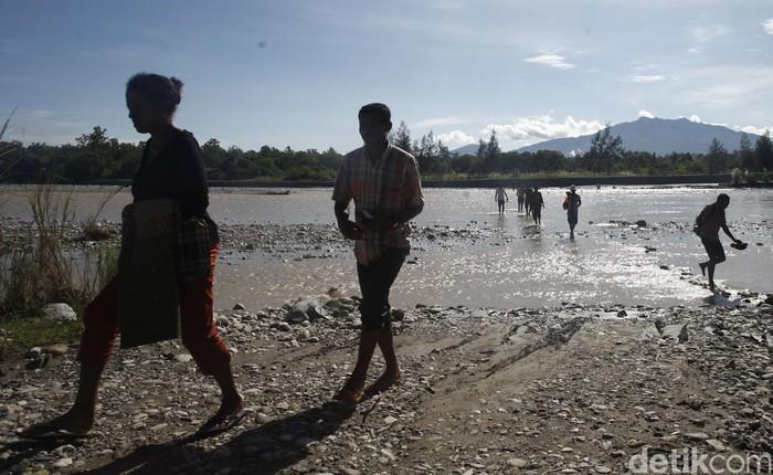 Puluhan warga Timor Leste terlihat melintas di sungai Malibaka menuju Atambua, Indonesia. Mereka nekat menyebrang sungai deras untuk berbelanja di Pasar Turiskain.