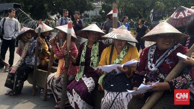 Sembilan orang kartini Kendeng melakukan aksi pukul lesung memprotes pembangunan pabrik semen Kendeng, di depan Istana Kepresidenan, 2017.
