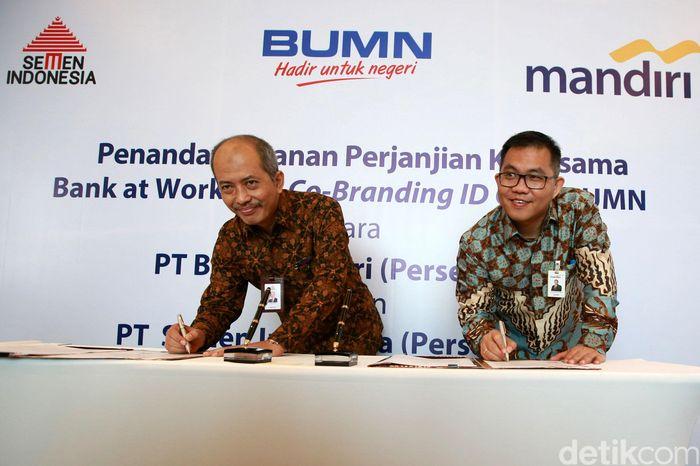 Direktur SDM dan Hukum PT Semen Indonesia Agung Yunanto (kiri) dan Direktur Digital Banking & Techology Bank Mandiri Rico Usthavia Frans (kanan) menandatangani kerja sama.