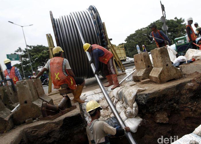Pekerja menarik gulungan kabel 150 kV untuk dipasang di dalam tanah.