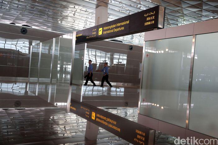 Dua pekerja melintas di terminal keberangkatan internasional, Senin (24/4/2017).