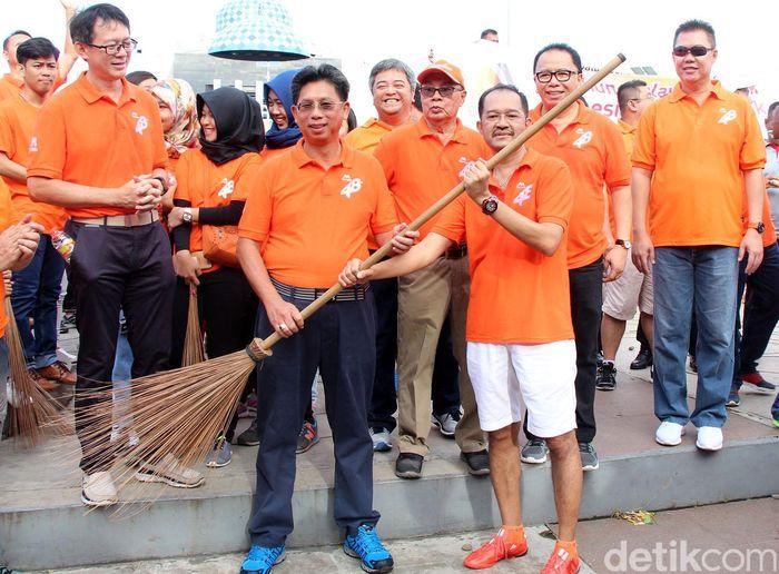 Direktur Utama Bank Mega Kostaman Thayib menyerahkan sapu kepada Ketua Mega Club Makassar Suhardi menandai dimulainya kegiatan bersih-bersih sampah di sekitar anjungan Pantai Losari. Pool/Banak Mega.