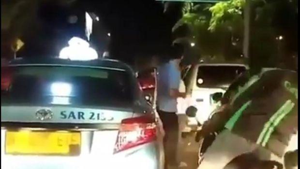 Sopir taksi dan pengemudi mobil berkelahi di tengah jalan.