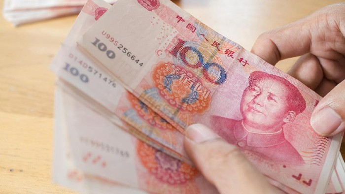 Man hand counting Chinese Yuan bank notes currency.