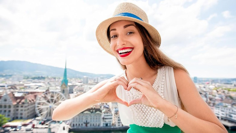 Young female tourist showing heart shape sitting on the top of the tower in Zurich city. Woman having a great vacation in Switzerland