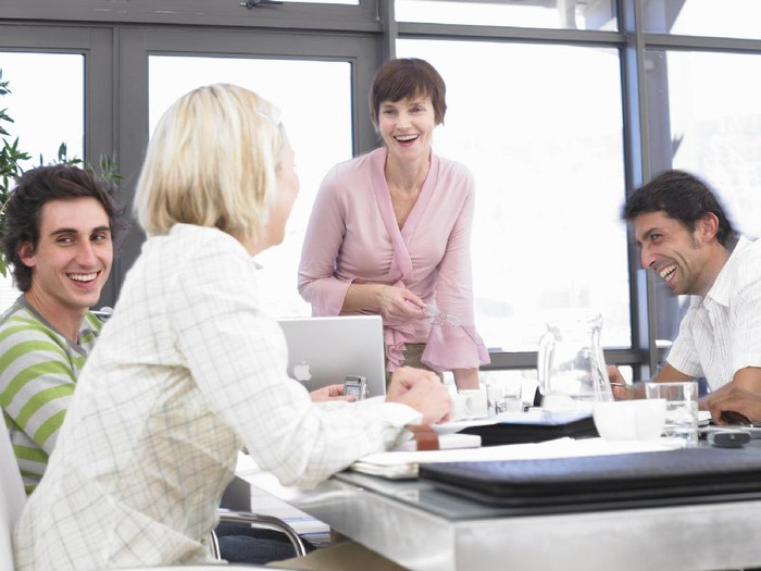 Businesswomen and men laughing sitting at conference table