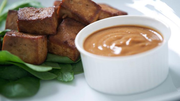 Indonesian marinaded tofu with peanut satay sauce on a small bed of spinach.