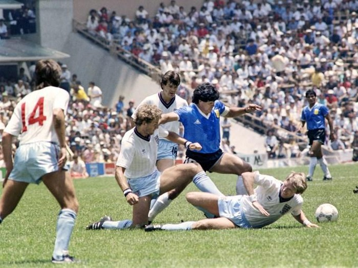 Argentinian midfielder Diego Maradona (C) dribbles past three English defenders on June 22, 1986 in Mexico City during the World Cup quarterfinal soccer match between Argentina and England. Maradona scored two goals, the first one with his left hand as he jumped for the ball in front of goalkeeper Peter Shilton, as Argentina beat England 2-1. / AFP PHOTO / STAFF