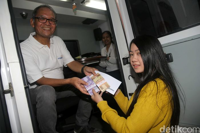Direktur Operations Bank Mandiri Ogi Prastomiyono tengah berbincang dengan pemudik usai menarik dana tunai di unit mobil ATM keliling yang ditempatkan di Rest Area 19 tol Jakarta-Cikampek, Bekasi, Jawa Barat, Kamis (22/6).