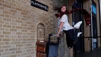 Menuju Hogwarts, seorang wanita berpose di Platform 9 3/4 Stasiun King Cross di London.