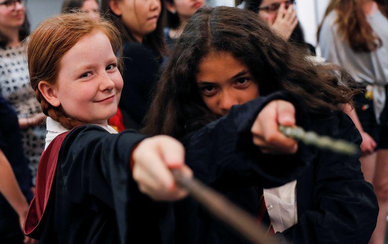 Dua orang anak nampak mengarahkan tongkat sihir ke arah kamera di Waterstones, London, selama peringatan 20 tahun Harry Potter. REUTERS/Neil Hall.