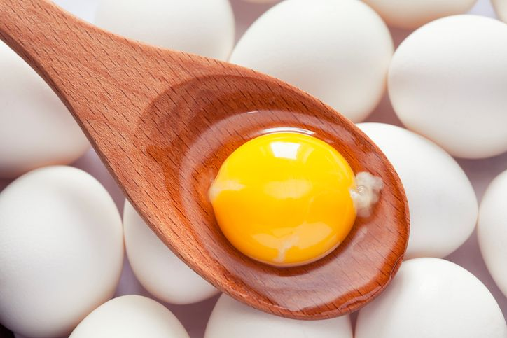Eggs and Egg yolk in paper tray on wood