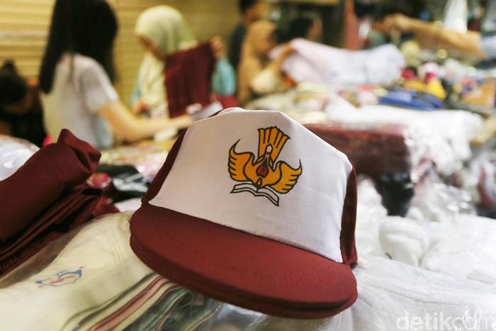 Calon pembeli mencoba baju seragam sekolah yang dijual di salah satu toko di Pasar Baru, Jakarta, Minggu (4/7). Sejumlah toko penjualan perlengkapan sekolah mulai dipenuhi orang tua siswa yang membeli seragam untuk tahun ajaran baru yang akan dimulai Senin (10/7). (Ari Saputra/detikcom)