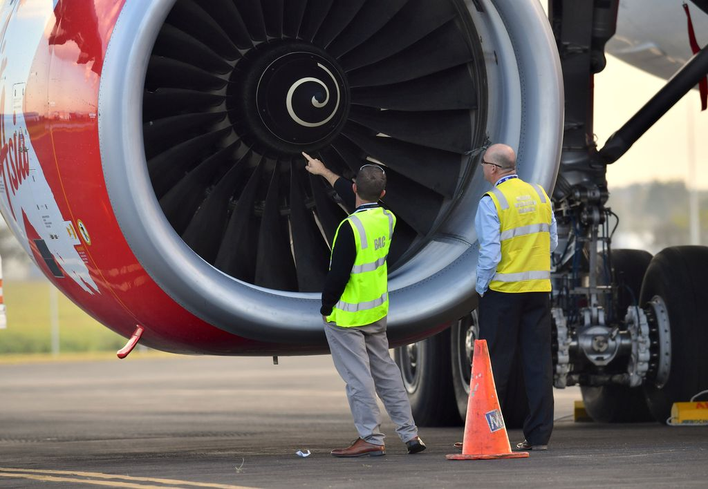 Officials inspect an engine of Malaysian budget carrier AirAsia X after it was diverted and forced to land because an engine was damaged during take-off by what was thought to be a bird strike at Brisbane Airport in Australia, July 4, 2017.    AAP/Darren England/via REUTERS    ATTENTION EDITORS - THIS IMAGE WAS PROVIDED BY A THIRD PARTY. NO RESALES. NO ARCHIVE. AUSTRALIA OUT. NEW ZEALAND OUT.     TPX IMAGES OF THE DAY