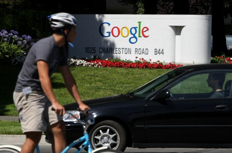 MOUNTAIN VIEW, CA - JULY 17:  A bicyclist rides by a sign outside of the Google headquarters July 17, 2008 in Mountain View, California. Google Inc. is expected to announce an increase in quarterly profits when it reports its quarterly earnings today after the closing bell.  (Photo by Justin Sullivan/Getty Images)