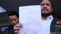 Sang pengacara menunjukkan laporan yang dibuat atas nama kliennya, Aris. Foto: Hanif Hawari