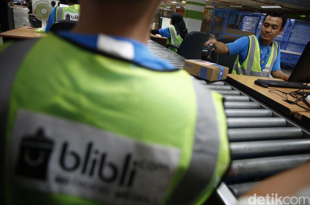 Seorang pekerja mengecek kualitas dan pengemasan barang yang akan dikirim.
