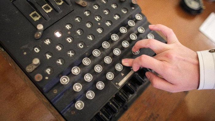 An employee of an auction house presses a key on an working original Enigma cipher machine that is on display at an auction house in Bucharest, Romania, July 11, 2017. Inquam Photos/Octav Ganea/via REUTERS ATTENTION EDITORS - THIS IMAGE WAS PROVIDED BY A THIRD PARTY. ROMANIA OUT.  TPX IMAGES OF THE DAY