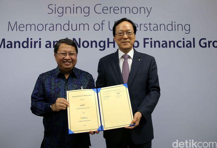 Wakil Direktur Utama Bank Mandiri Sulaiman A Arianto (kiri) dan Chairman & CEO NongHyup Financial Kim Yong Hwan (kanan) usai penandatanganan nota kesepahaman sejumlah bisnis perbankan di Plaza Mandiri, Jakarta (17/7/2017).