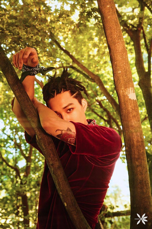 Kai tampil dengan kemeja merah di antara pepohonan. (Dok. Twitter/@EXO)