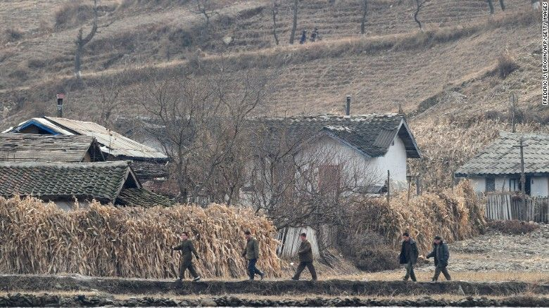North Korean men walk amid a dry and barren landscape on the banks of the Yalu River in November 2010. (Frederic J Brown/AFP/Getty Images)