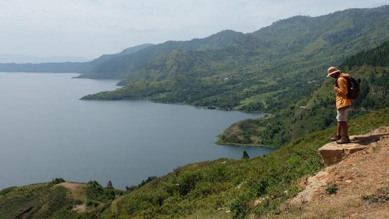 Wistawan yang menikmati Danau Toba (I Gede Leo Agustina/ dTraveler)