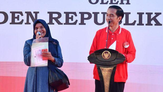 Jokowi membagikan sertifikat tanah, ada pin di jaketnya.