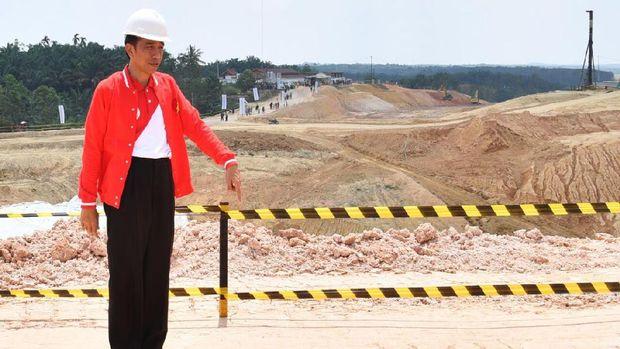 Jokowi saat meninjau pembangunan tol mengenakan jaket berlogo 'The Flash'.