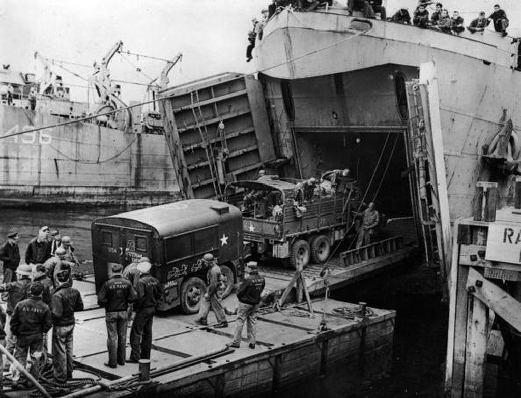 Kendaraan tempur dan logistik dimasukkan ke kapal yang akan menggempur pertahanan Jerman di Perancis. Pasukan yang terlibat berasal dari Amerika Serikat, Inggris, Kanada, Australia dan sebagainya. Foto: Getty Images