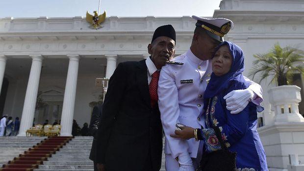 Seorang taruna TNI AL bersama keluarga usai upacara Prasetya Perwira Akademi TNI dan Polri 2017, di halaman Istana Merdeka, Jakarta, Selasa (25/7/2017)