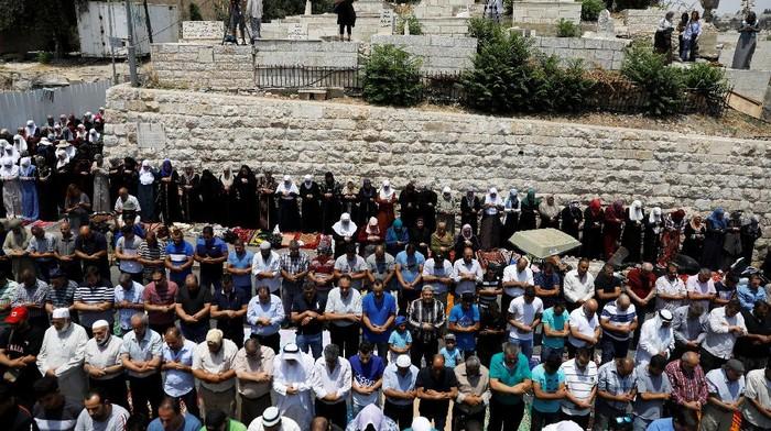 Jemaah memilih salat di luar Masjid Al-Aqsa (REUTERS/Ronen Zvulun)