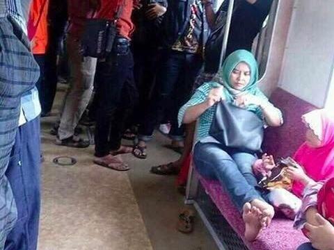 Seorang penumpang duduk selonjoran di bangku KRL yang jadi viral