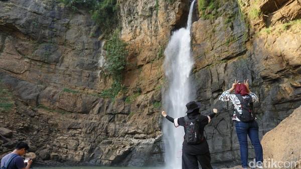 Wisatawan yang berkunjung ke Curug Cimarinjung bisa berfoto-foto dengan latar belakang air terjun itu. Meski seru, tetapi tetap utamakan keselamatan ya traveler! (Mukhlis/detikTravel)
