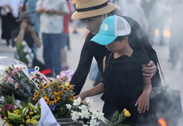 Foto: Orang-orang sudah ramai datang sebelum acara memorial dimulai. Mereka memang banyak berdoa di sana dan membawa buket bunga. Karangan bunga pun berjejer di depan tugu (Jiji Press/AFP)